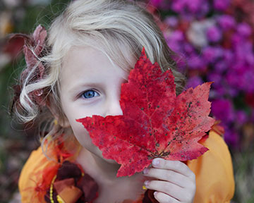Child holding a red leaf