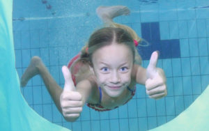 Little girl underwater doing thumbs up